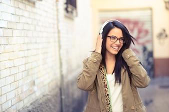 Chica morena con gafas escuchando música con auriculares