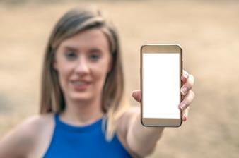 Chica mostrando una pantalla de teléfono inteligente en blanco