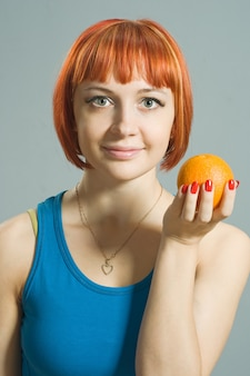 Chica pelirroja con naranja