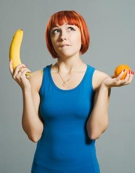 Chica pelirroja con plátano y naranja