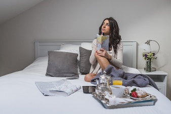 Chica pensando antes de escribir en su cuaderno