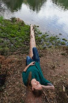 Chica relajada tumbada en un tronco