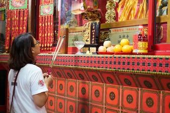 Chica rezando en un templo