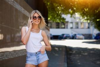 Chica rubia con gafas de sol hablando por teléfono