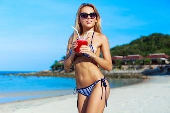 Chica rubia con gafas de sol sujetando su refrescante bebida