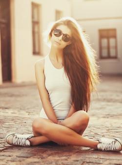 Chica rubia sentada con las piernas cruzadas