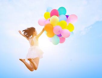 Chica saltando con globos
