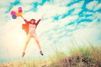 Chica saltando en la playa con globos de colores
