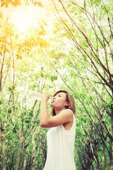 Chica sedienta bebiendo agua con ramas de los árboles de fondo