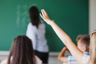 Chica sentada en el aula levantando la mano