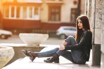 Chica sentada y apoyada en una columna