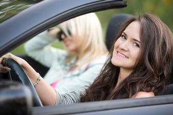 Chica sonriendo conduciendo un coche descapotable