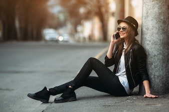 Chica sonriendo mientras habla por su móvil sentada en el suelo
