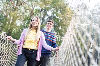 Chica sonriente cruzando el puente con su amigo