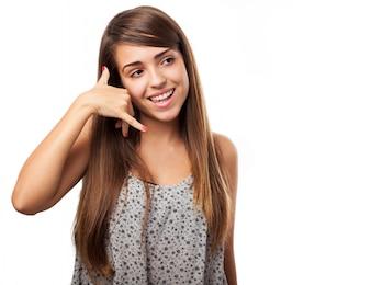 Chica sonriente haciendo el gesto de llámame