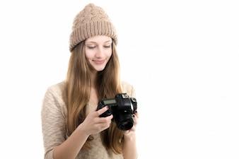 Chica sonriente revisando algunas fotos en su cámara