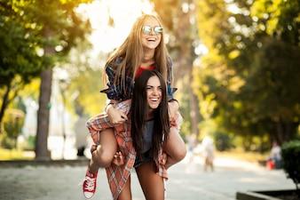 Chica subida a caballito en la espalda de su amiga
