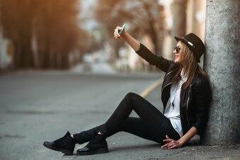 Chica tomándose un selfie sentada en el suelo