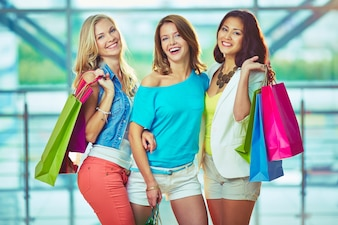 Chicas alegres con bolsas de la compra