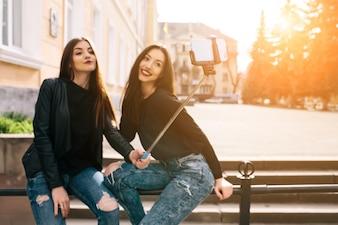 Chicas con un palo para selfies