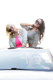 Chicas de pie en un coche descapotable con gafas de sol