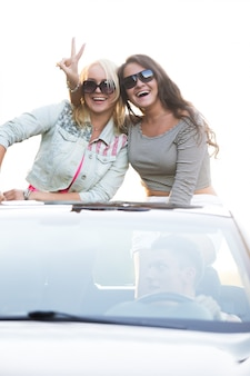 Chicas de pie en un coche descapotable