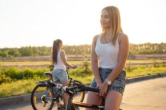 Chicas en bicicleta mirando en direcciones opuestas