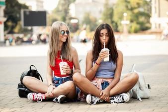 Chicas jóvenes sentadas en el suelo con un refresco en la mano