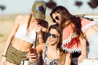 Chicas jóvenes sonriendo sentadas en un coche mirando un teléfono inteligente