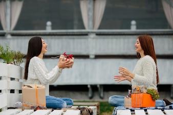 Chicas lanzandose entre ellas un regalo marrón