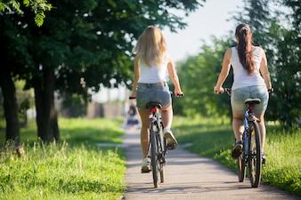 Chicas montando en bici desde atrás