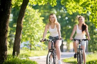 Chicas montando en bici y sonriendo