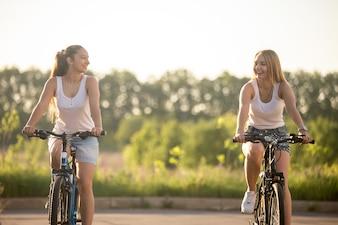 Chicas riendo en bicicleta
