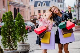 Chicas rubias con bolsas de pie sonriendo