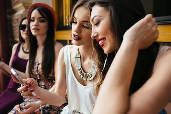 Chicas sonriendo miran un teléfono