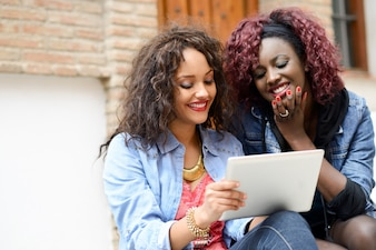 Chicas usando una tableta al aire libre