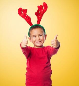 Chico alegre con una diadema de reno y los pulgares para arriba