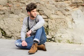 Chico atractivo sentado en el suelo