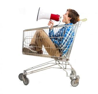 Chico con un megáfono en un carro de la compra