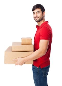 Chico sonriente sujetando algunas cajas