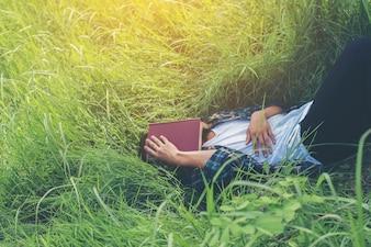 Chico tumbado en la hierba con un libro en la cara