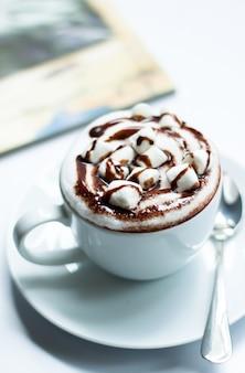 Chocolate caliente con malvavisco en la mesa blanca