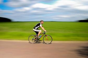 Ciclista en movimiento y un cielo nublado