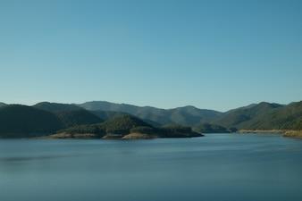 Cielo azul y montaña en el agua