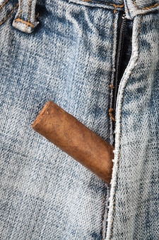 Cigarro fuera de la cremallera de los pantalones vaqueros