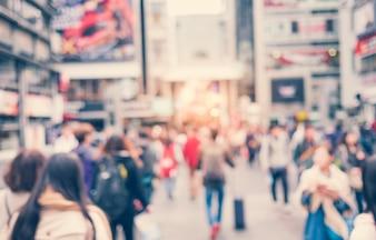 Ciudad con personas caminando desenfocadas