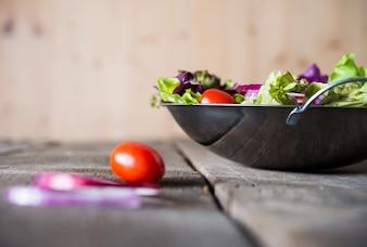 Close up de ensalada de verduras frescas en el recipiente con fondo de madera rústica de edad. Concepto de alimentos saludables.