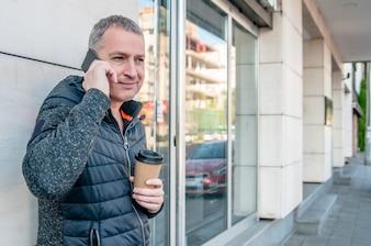 Close up retrato de hombre maduro feliz hablando por teléfono celular y sonriente