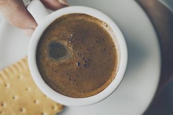Closeup de café sabroso expreso con sabrosa espuma en la pequeña taza de cerámica. Mujeres manos sosteniendo caliente bebida caliente.
