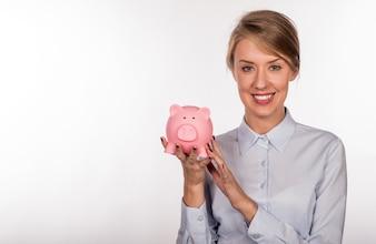 Closeup retrato feliz, sonriente mujer de negocios, la celebración de hucha rosa, aislado en el interior de oficina de fondo. Ahorro presupuestario financiero, concepto de inversión inteligente